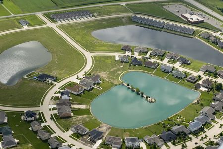 The curving streets of a suburban housing development\rsurround a small blue pond, as seen from the air.