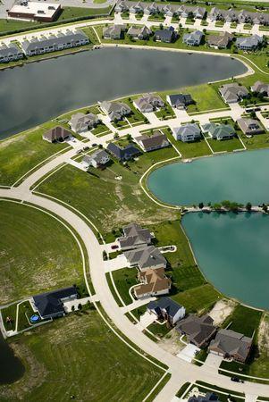 교외 주택 개발의 커브 스트리트는 공기에서 볼 수 있듯이 작은 푸른 연못을 둘러싼 다. 스톡 콘텐츠