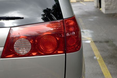 taillight: Close up of a red passenger side tail light on a parked silver car.