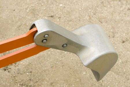 A close up of an orange and silver toy bulldozer in a sandbox.