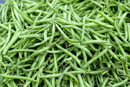 Long green beans heaped at a market.  photo