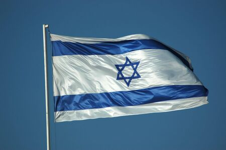 israeli: The Israeli flag flying against a bright blue sky. Stock Photo