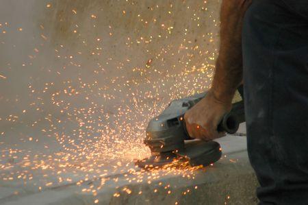 샌더가 콘크리트를 때리면 불꽃이 날아간다.