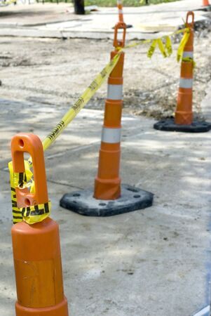 Three orange road cones bound by a yellow caution tape.   photo