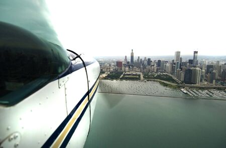 aluminum airplane: Airplane flying over water approaching a city