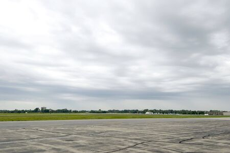 Wide shot of empty airport runway with cloudy sky