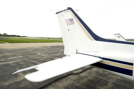aluminum airplane: Blue, white and tan tail of plane on cement runway