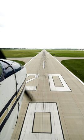 rightwing: Right-wing view of a white airplane with a tan and blue stripe landing on runway 20
