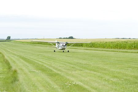 Image of a small aircraft landing on green field