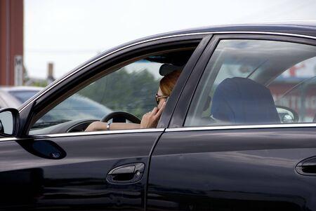 여자가 운전하는 동안 휴대 전화에 이야기