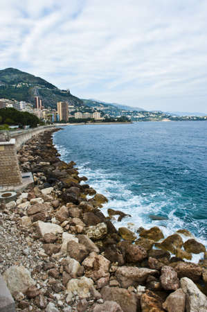 Green algae and rocks along the Mediterranean Sea, in a cloudy sky overlooking the Monaco principality.  photo