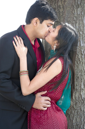 A young and happy Indian couple kissing near a tree in the Fall on a cloudy day. Banque d'images