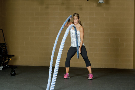 athlete woman: An attractive young and athletic girl using training ropes in a gym.