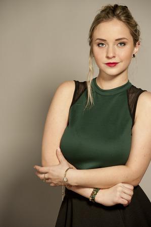 minijupe: Belle jeune femme brune plantureuse femme avec des cheveux redressé dans un studio tout en portant un haut vert et une mini jupe courte noire sur un fond gris.
