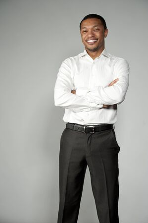 slacks: An attractive and happy African American boy wearing a white button down and black slacks on a gray background in a studio setting acting funny.