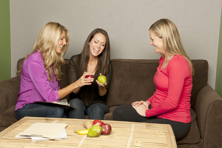 A pair of nutritionist consult a pregnant female on a couch. 免版税图像