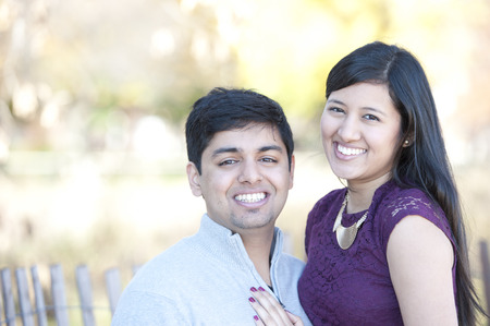 A young and happy Indian couple portrait with a Fall background on a sunny day.