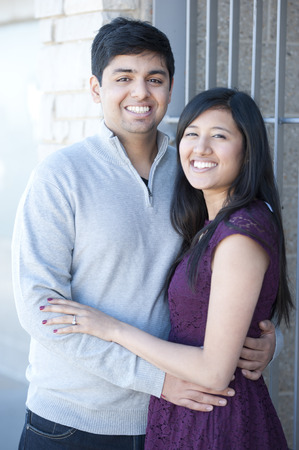 A young and happy Indian couple on a metal steel gray background on a sunny day. Stock Photo