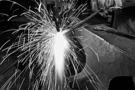 acetylene: A metal fabricator utilizing a torch to heat up a piece of metal in order to shape it.
