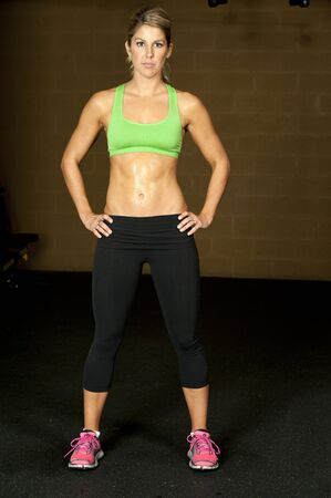 yoga pants: A fit and young muscular brunette wearing black yoga pants and a green sports bra in a gym.