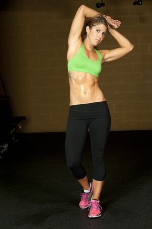 A fit and young muscular brunette wearing black yoga pants and a green sports bra in a gym.
