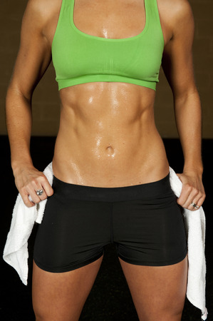 Athletic and toned female abs and upper body in a gym.