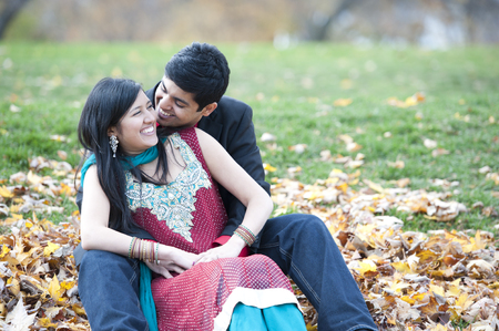 A young and happy Indian couple posing on a pile of leaves in the fall on a cloudy day.