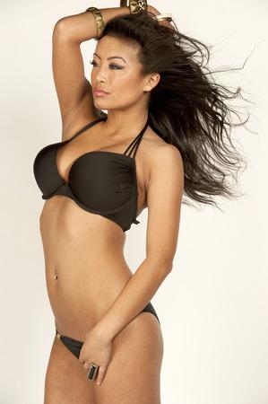 Eine asiatische Badeanzug Modell trägt ein schwarzes 2 Stück Badeanzug auf weißem Hintergrund in den Wind. Standard-Bild