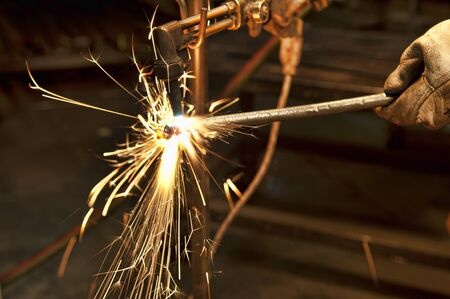 fabricator: A metal fabricator utilizing a torch to heat up a piece of metal in order to shape it.