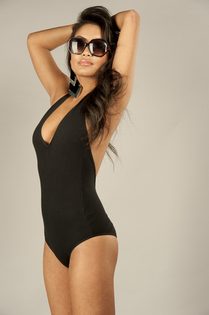 A beautiful young swimsuit model wearing a one piece black bathing suit and sunglasses.