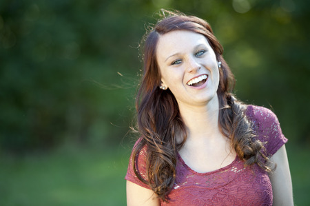 sociable: A happy young brunette girl posing outdoors with a green background on a sunny day. Stock Photo