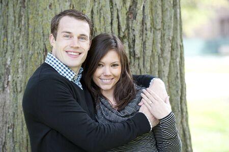 donne mature sexy: Una coppia felice, giovane e attraente guardando la telecamera in una giornata di sole in un parco