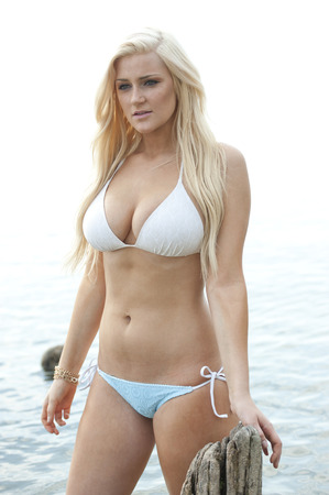 Young gorgeous blond busty model wearing a chic white bathing suit on a sunny day at the beach.
