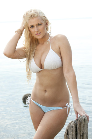 busty: Young gorgeous blond busty model wearing a chic white bathing suit on a sunny day at the beach.