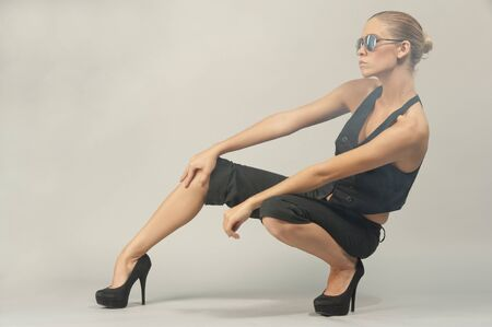 crouching: A young female model crouching on a gray background in a studio setting while wearing sunglasses and a black outfit. Stock Photo