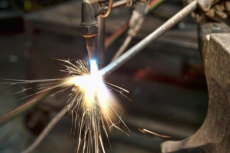 soldadura: Un fabricante de metal, utilizando un soplete para calentar una pieza de metal con el fin de darle forma.