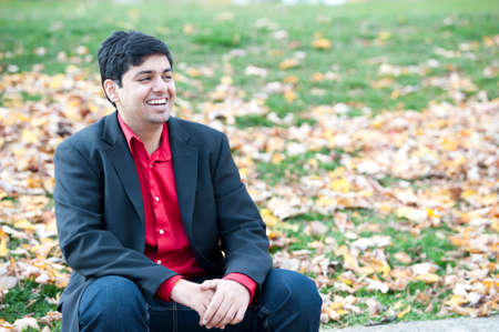 asian man: A young attractive Indian man sitting outdoors on a cloudy day in the fall.
