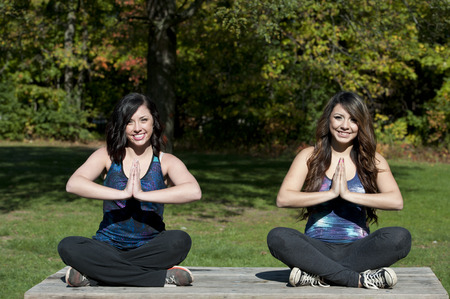 dhyana: A meditation yoga pose performed by young girls at the park. Stock Photo