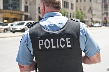 police badge: A Chicago city policeman standing on the road on a sunny day wearing a bullet proof vest mentioning Police on his body.  Stock Photo
