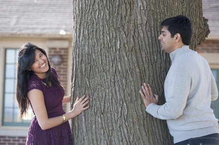 A young and happy Indian couple wearing modern attire looking for each other around a tree.