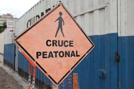 paso peatonal: Paso de peatones signo escrito en español en un día nublado. Foto de archivo