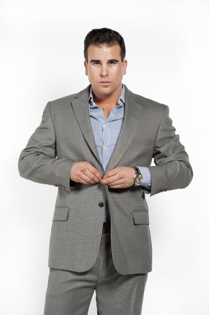 Athletic and attractive caucasian male wearing a fitted gray suit with a blue button down shirt in a studio setting on a white background posing and looking at the camera and buttoning his suit. Stock Photo