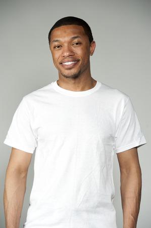 재미 행동 회색 배경에 스튜디오 설정에서 간단한 흰색 셔츠를 입고 행복 매력적인 흑인 남성.