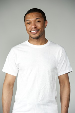 A happy attractive black male wearing a simple white t-shirt in a studio setting on a gray background acting funny. Stock Photo