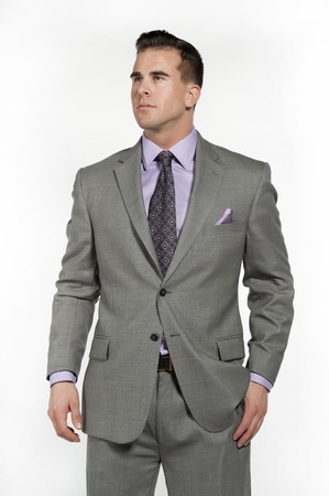 white suit: Attractive caucasian male fitness model wearing a trendy fitted and fashionable gray suit with a purple shirt and tie underneath posing in a studio on a white background while looking to the left.