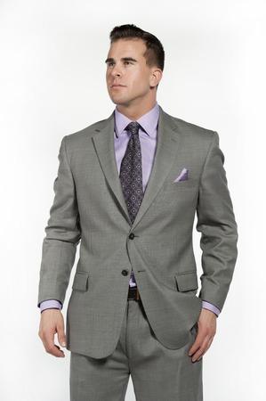 traje formal: Modelo de fitness caucásico atractivo masculino llevaba un traje gris equipada y de moda de moda con una camisa púrpura y corbata debajo posando en un estudio sobre un fondo blanco, mientras que mirando a la izquierda.