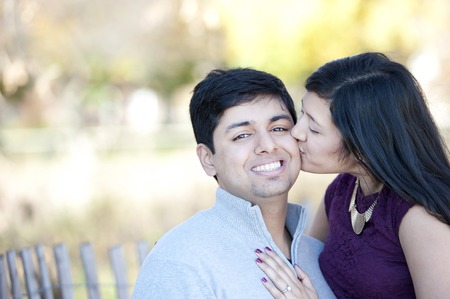 fiance: A young and happy Indian girl kissing her fiance with a Fall background.