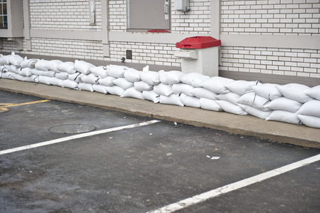 A pile of sandbags stacked to protect a restaurant on a cloudy day. 免版税图像