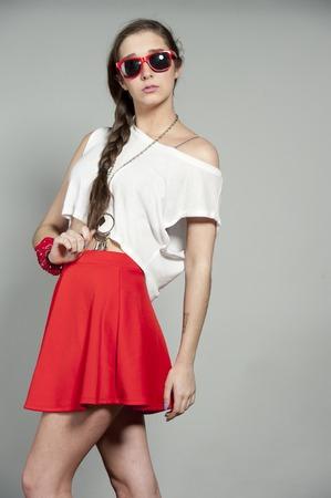 minifalda: Atractiva chica morena que llevaba un par de gafas de sol rojas, camiseta blanca y una mini falda roja sobre un fondo gris del estudio.