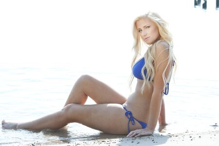 tetona: Una bella modelo joven y atractiva mujer rubia que llevaba un traje de baño azul en un día soleado en la playa.